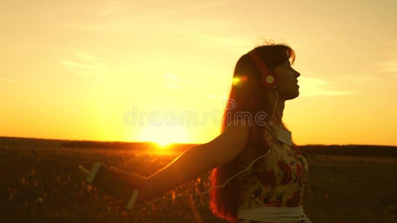 Jong meisje in hoofdtelefoons en met een smartphoneroes tijdens de vlucht onder de stralen van een warme zonsondergang Langzame M stock afbeelding