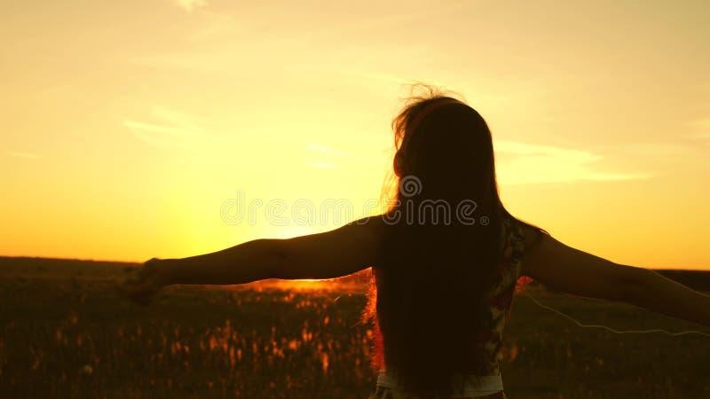 Jong meisje in hoofdtelefoons en met een smartphoneroes tijdens de vlucht onder de stralen van een warme zonsondergang Langzame M royalty-vrije stock afbeelding