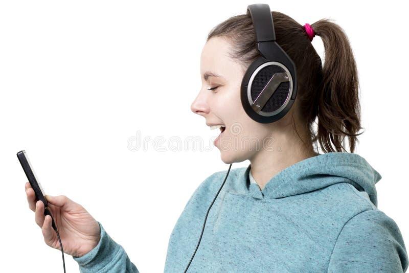 Jong meisje in hoofdtelefoons met speler die in handen m luisteren te knallen royalty-vrije stock afbeelding
