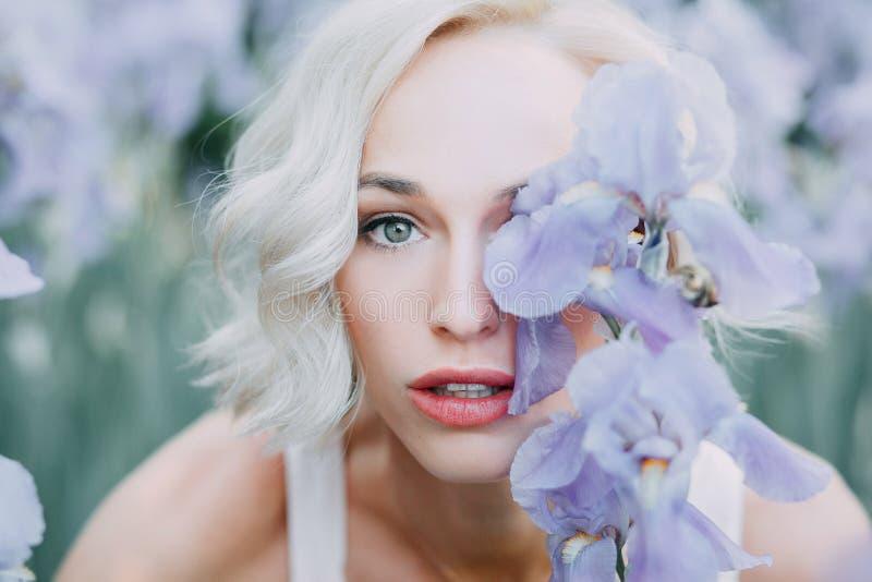 Jong meisje in irisbloemen stock afbeeldingen
