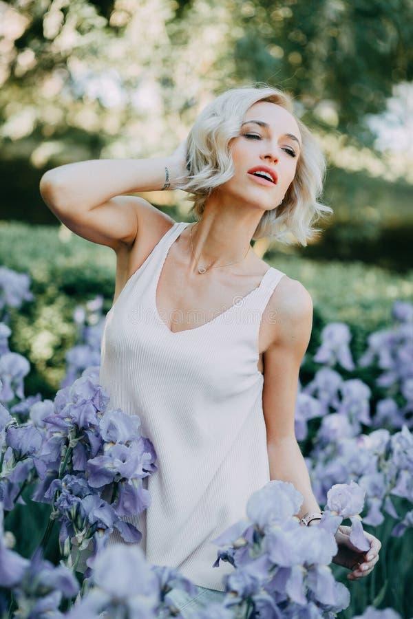 Jong meisje in irisbloemen stock foto