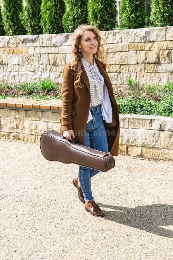 Jong meisje in laag met geval voor viool ter beschikking royalty-vrije stock afbeeldingen