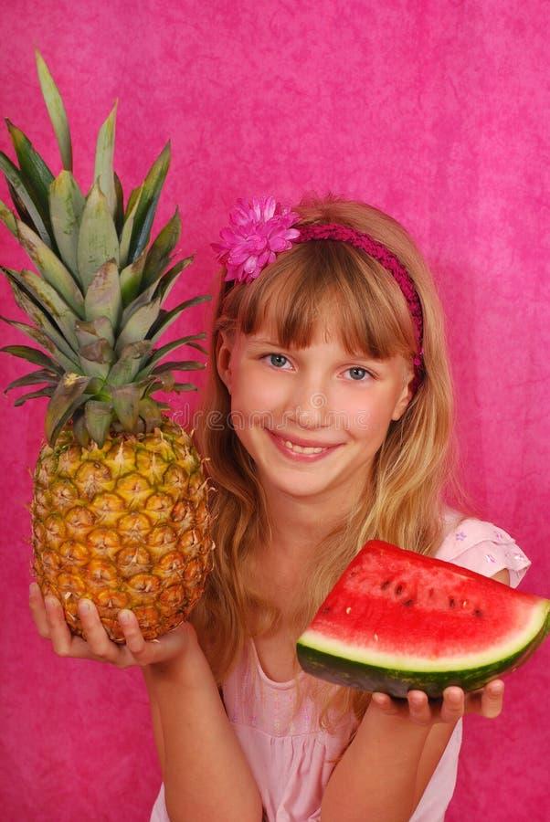 Jong meisje met ananas en watermeloen stock afbeelding