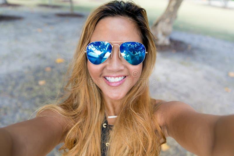 Jong meisje met blauwe spiegelzonnebril die selfie uit handen nemen stock foto