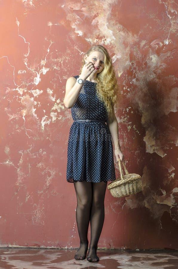 Jong meisje met blonde krullend haar in een lange kleding met stippen wiiiiiiiiiiith een mand stock fotografie