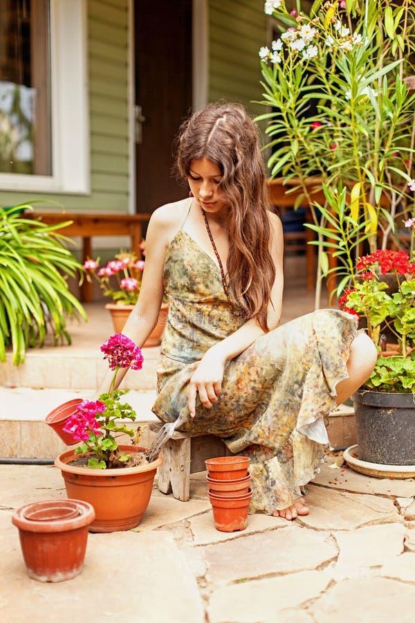 Jong meisje met de lange bruine geraniums van haartransplantaties in kleipotten stock foto