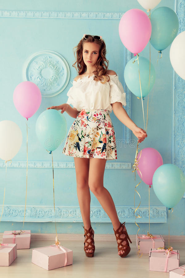 Jong meisje met donker krullend haar en tedere make-up, die met kleurrijke luchtballons stellen stock foto's