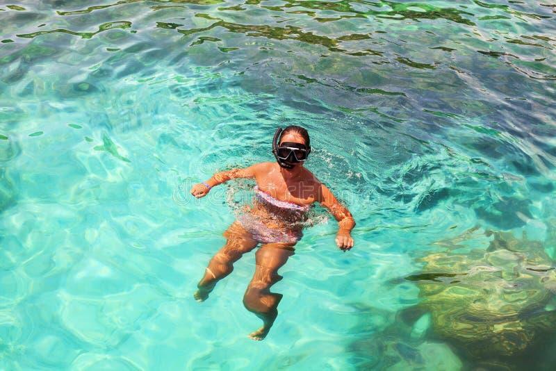 Jong meisje met duikmasker en snorkel duiken in helder blauw zeewater, volwassen vrouw in wit bikini zwemt in turkooizen schoon w stock afbeeldingen