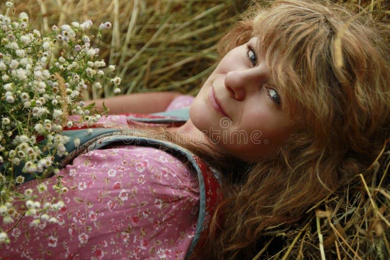 Jong meisje met een boeket van bloemen in aard dichtbij het hooi royalty-vrije stock fotografie
