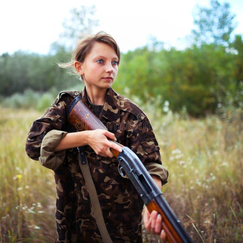 Jong meisje met een jachtgeweer in openlucht stock afbeeldingen