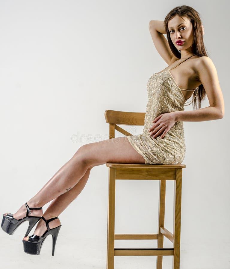 Jong meisje met een mooi cijfer in in gouden kleding in nauwsluitende miniskirt en hoog hielen en platform stock foto's