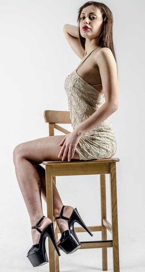 Jong meisje met een mooi cijfer in in gouden kleding in nauwsluitende miniskirt en hoog hielen en platform stock fotografie