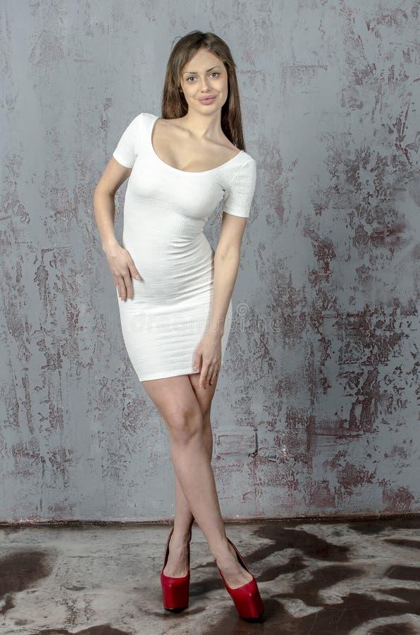 Jong meisje met een mooi cijfer in in witte kleding in nauwsluitende miniskirt en rode hoge hielen en gekleed platform royalty-vrije stock foto