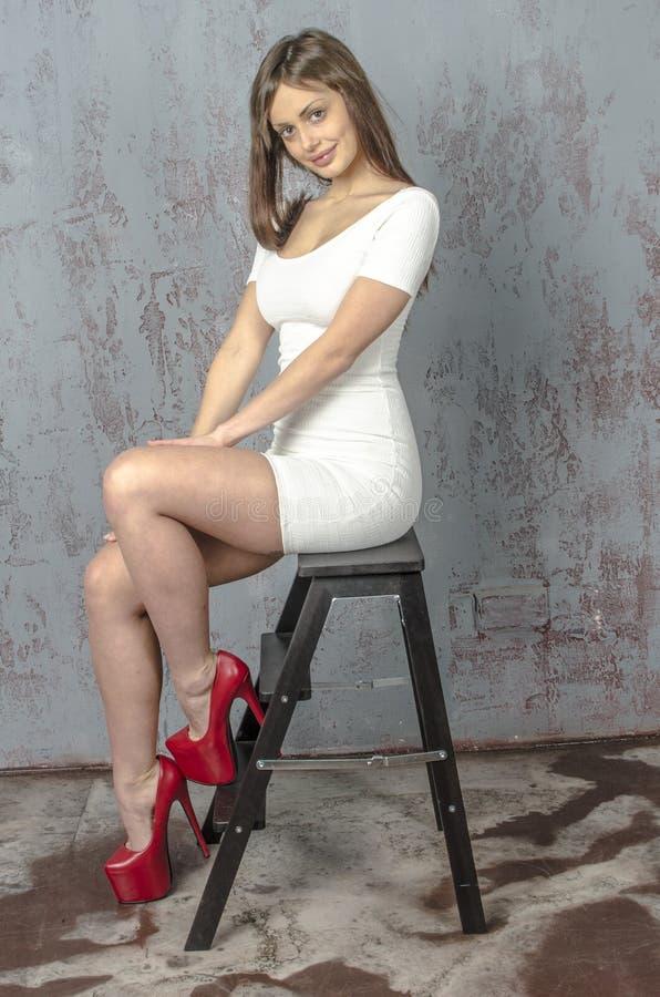 Jong meisje met een mooi cijfer in in witte kleding in nauwsluitende miniskirt en rode hoge hielen en gekleed platform stock afbeelding
