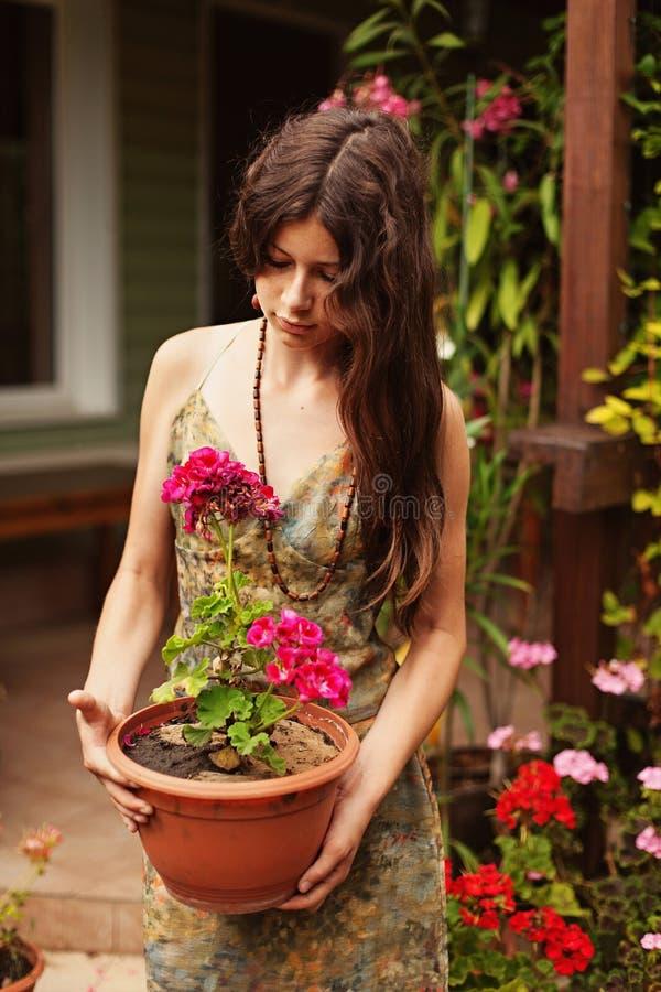 Jong meisje met een pot van geranium royalty-vrije stock foto's