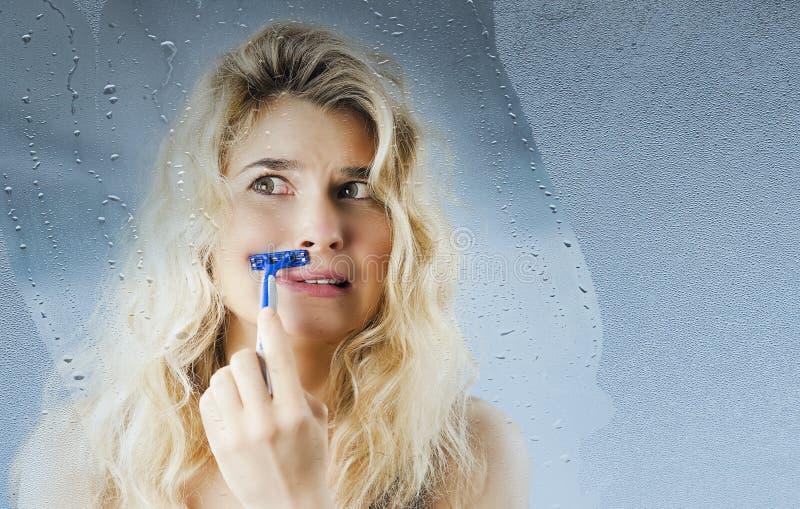 Jong meisje met een scheermes in hand scheerbeurten na het nemen van een douche op een achtergrond Conceptenschoonheid en huidzor stock afbeelding