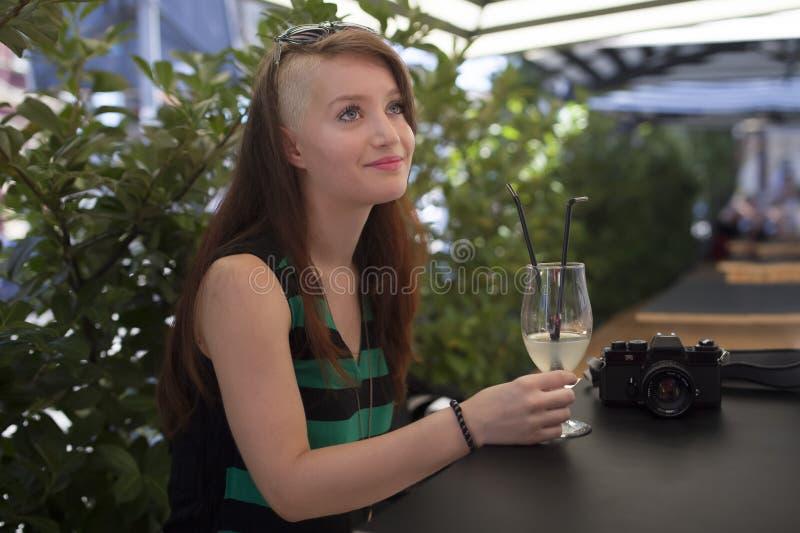 Jong meisje met fotocamera in een caffe die van de zomer genieten stock afbeeldingen
