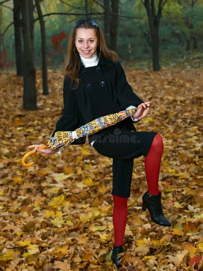 Jong meisje met gele paraplu in daling openlucht royalty-vrije stock afbeeldingen