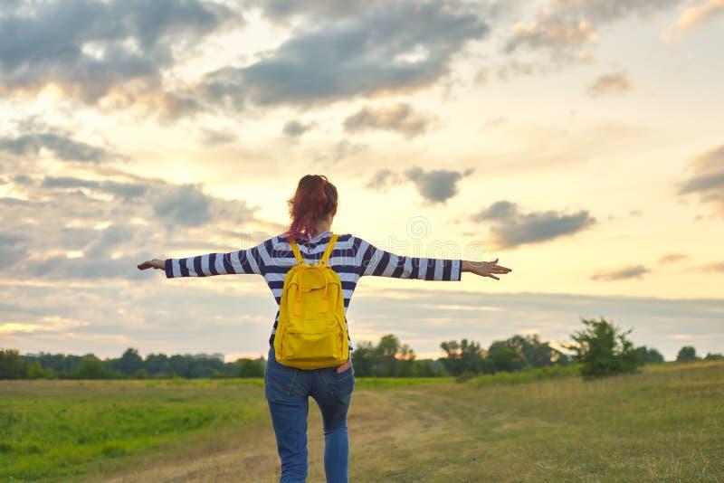 Jong meisje met gele rugzak, haar terug met open handen stock afbeelding
