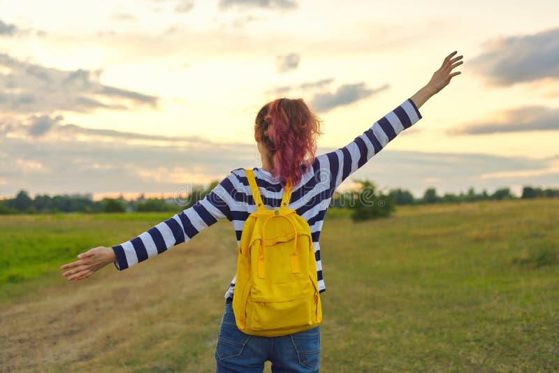 Jong meisje met gele rugzak, haar terug met open handen stock foto's