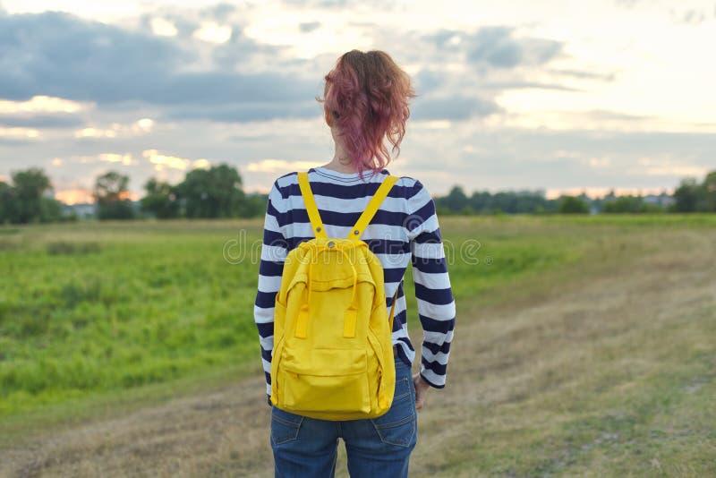 Jong meisje met gele rugzak, rug die, zonsonderganghemel gelijk maken stock afbeelding