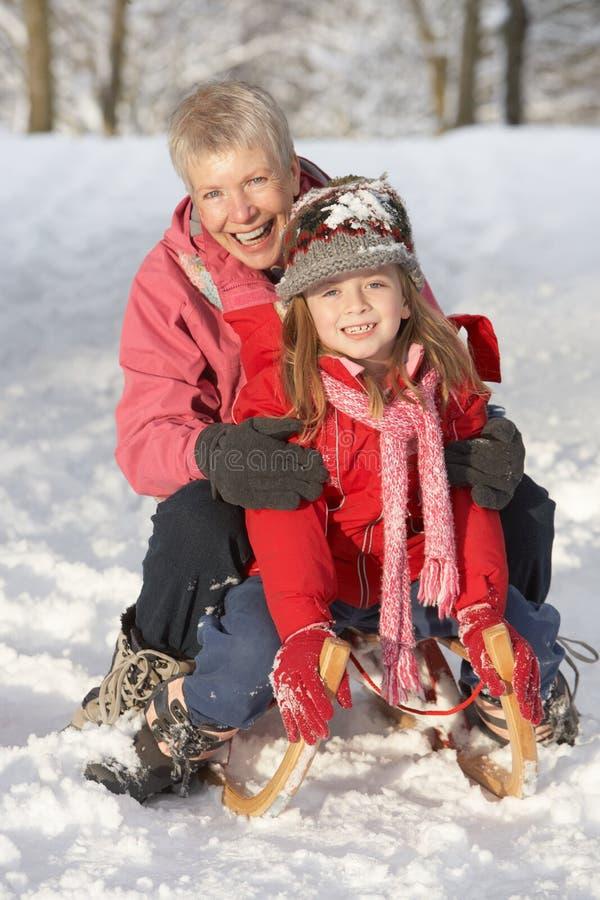 Jong Meisje met Grootmoeder die op Slee berijdt royalty-vrije stock foto