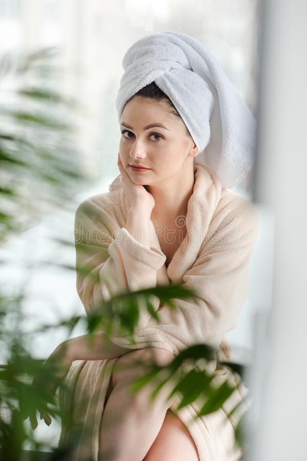 Jong meisje met grote ogen en donkere wenkbrauwen, in witte handdoek op hoofd lichte naakte make-up, schoonheidsfoto royalty-vrije stock afbeelding