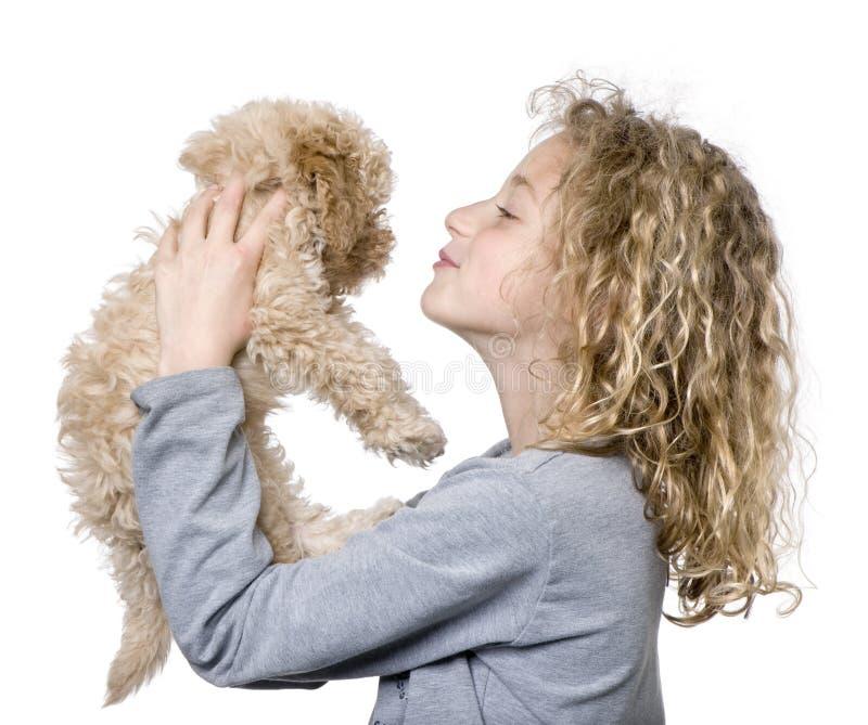 Jong meisje met haar stuk speelgoed puppy van de Poedel (9 weken oud) stock foto