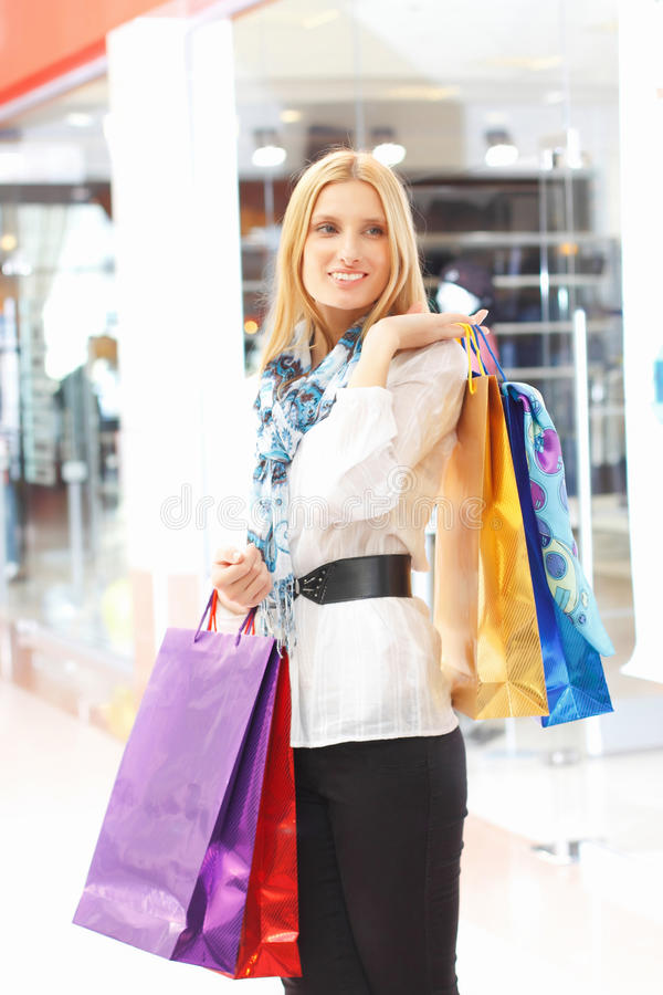 Jong meisje met het winkelen zakken stock foto's