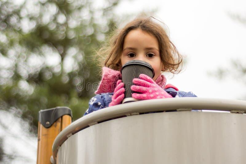 Jong meisje met hete drank bij een speelplaats die, gedeeltelijk haar gezicht behandelen stock foto