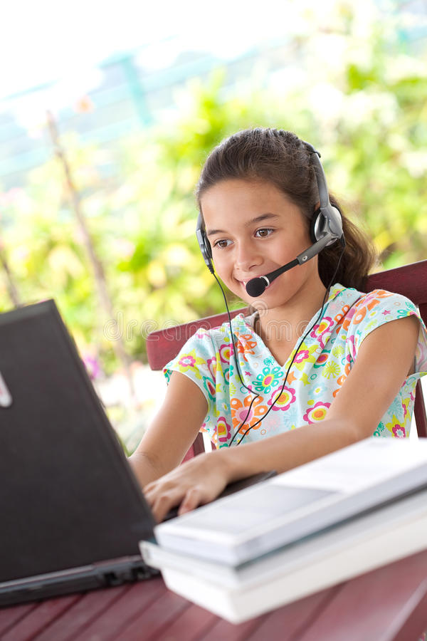 Jong meisje met hoofdtelefoon en het gebruiken van laptop stock afbeelding