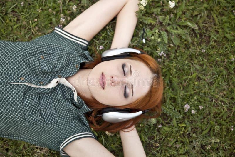 Jong meisje met hoofdtelefoons die bij groen gras liggen. stock afbeeldingen