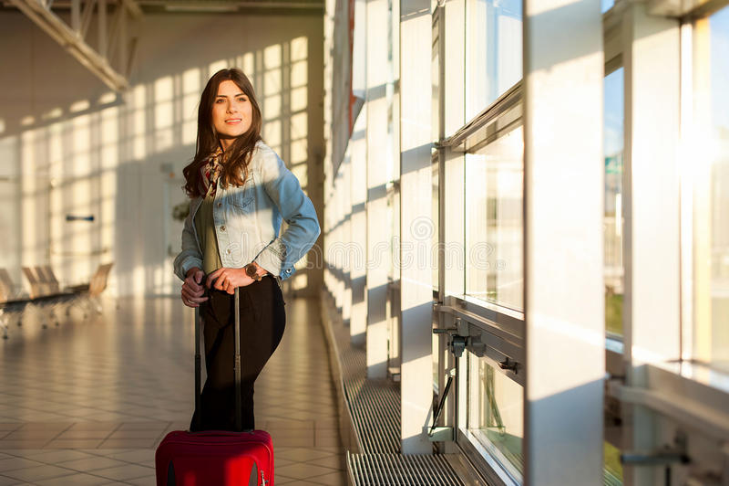 Jong meisje met karretjezak in luchthavenwachtkamer stock afbeelding