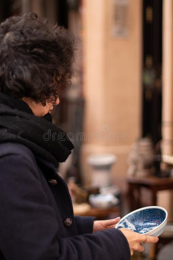 Jong meisje met laag en sjaal die een ceramische plaat in een antieke straatmarkt bekijken stock afbeeldingen