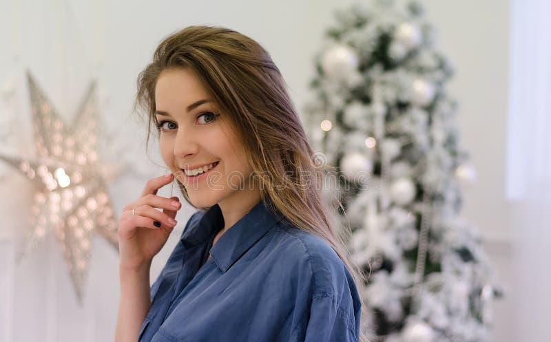 Jong meisje met lang blondy haar die blauw overhemd dragen onder een Kerstboom stock fotografie