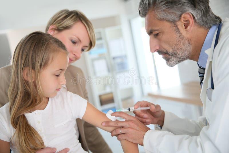 Jong meisje met moeder worden die die door arts wordt ingeënt stock fotografie