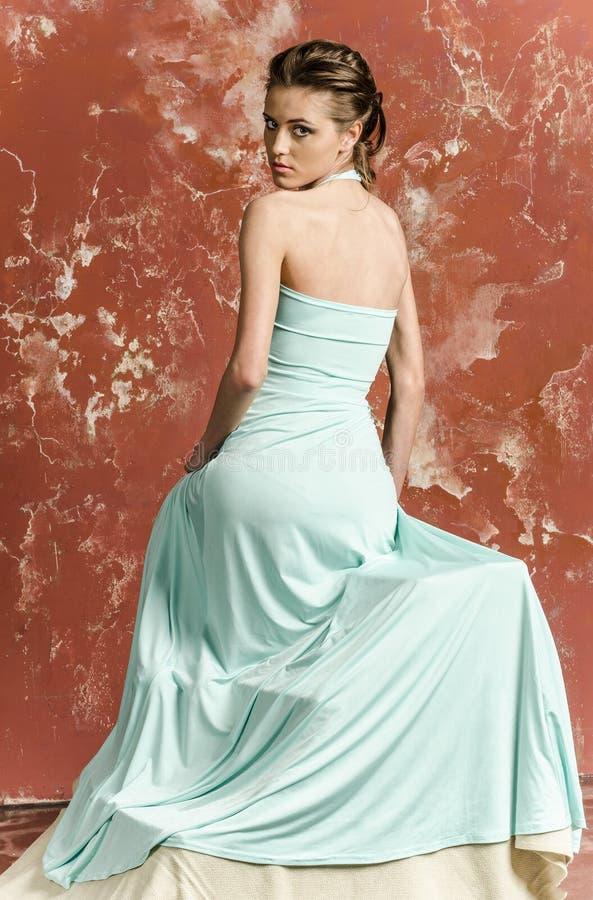 Jong meisje met mooi haar in een lange blauwe kleding en platformsandals stock afbeeldingen
