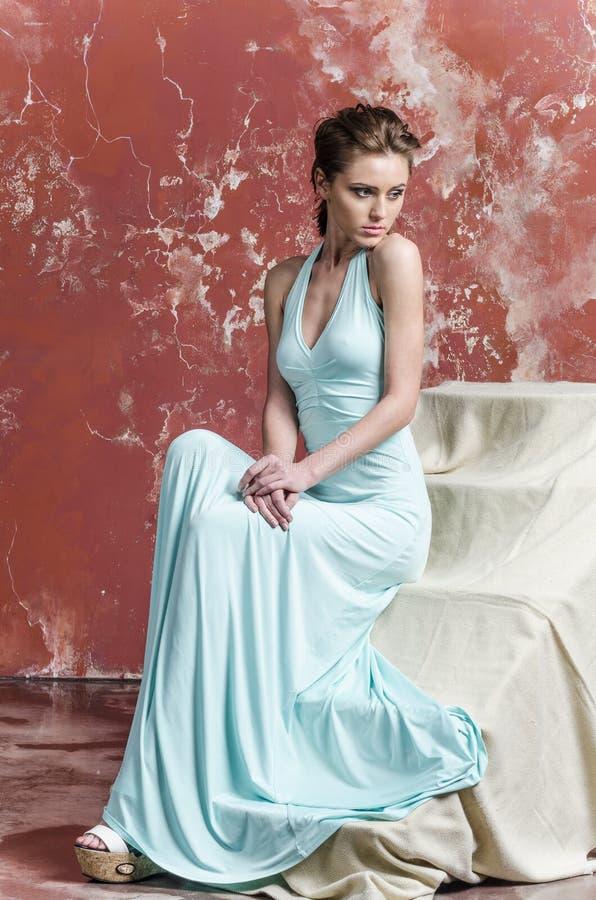 Jong meisje met mooi haar in een lange blauwe kleding en platformsandals royalty-vrije stock fotografie