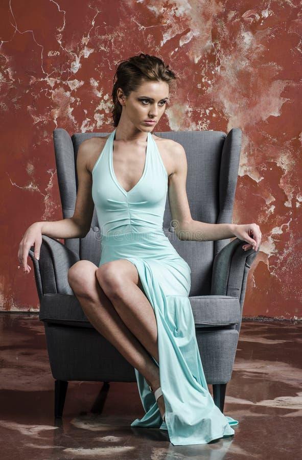 Jong meisje met mooi haar in een lange blauwe kleding en platformsandals stock fotografie