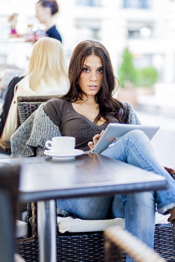 Jong meisje met tablet in restaurant stock afbeelding