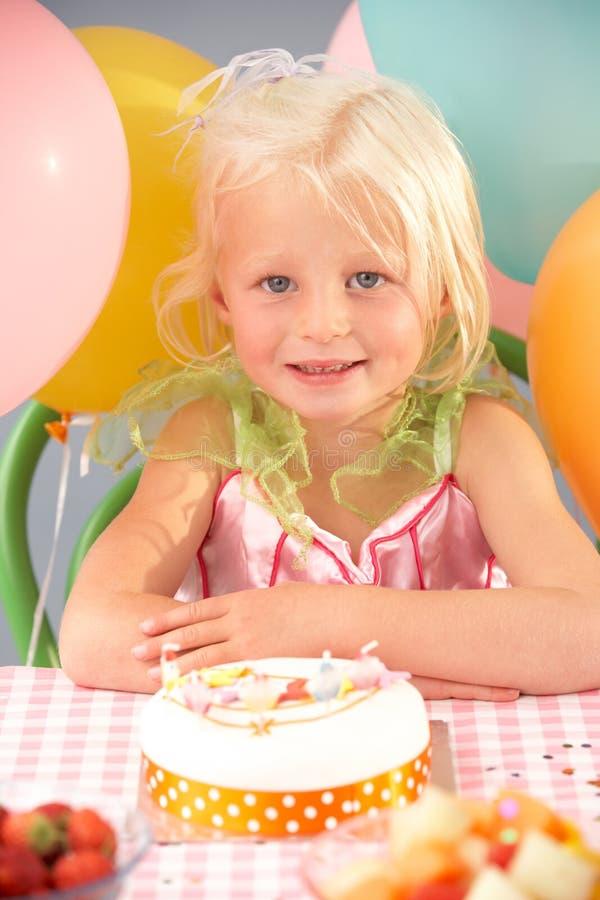 Jong meisje met verjaardagscake bij partij stock foto's
