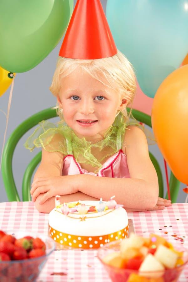 Jong meisje met verjaardagscake bij partij stock foto