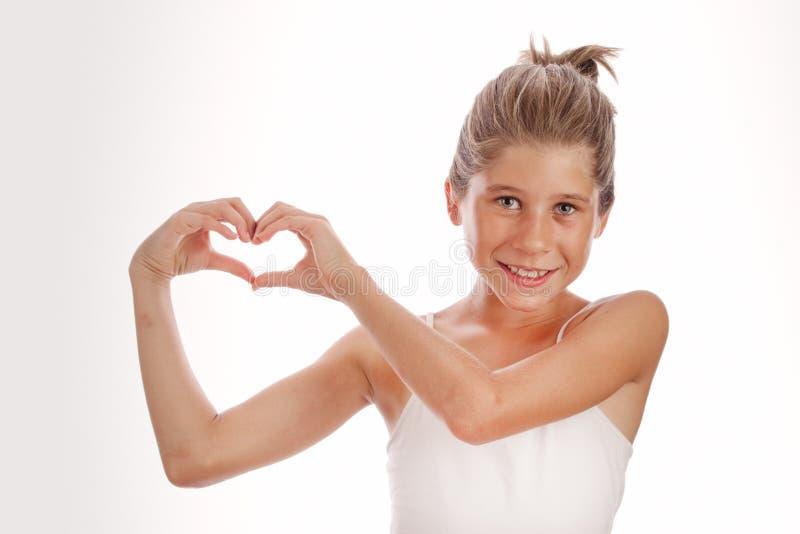 Jong meisje met witte die bovenkant op witte achtergrond met harthanden wordt geïsoleerd stock fotografie