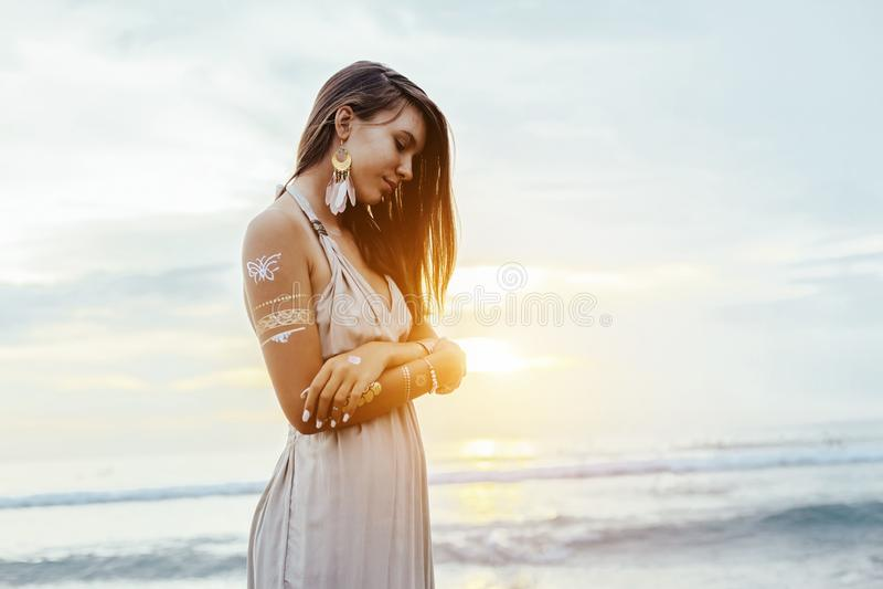 Jong meisje met zilveren tatoegering en bohojuwelen op zonsondergang royalty-vrije stock afbeeldingen