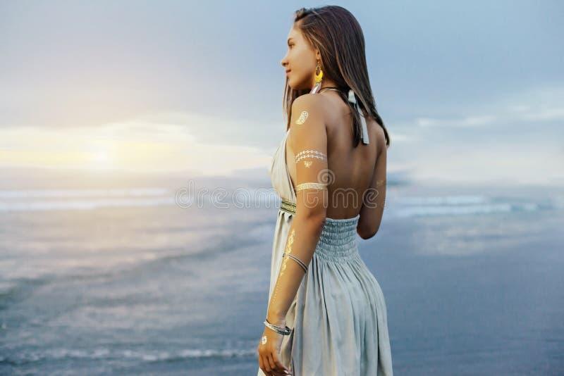 Jong meisje met zilveren tatoegering en bohojuwelen op zonsondergang royalty-vrije stock foto's
