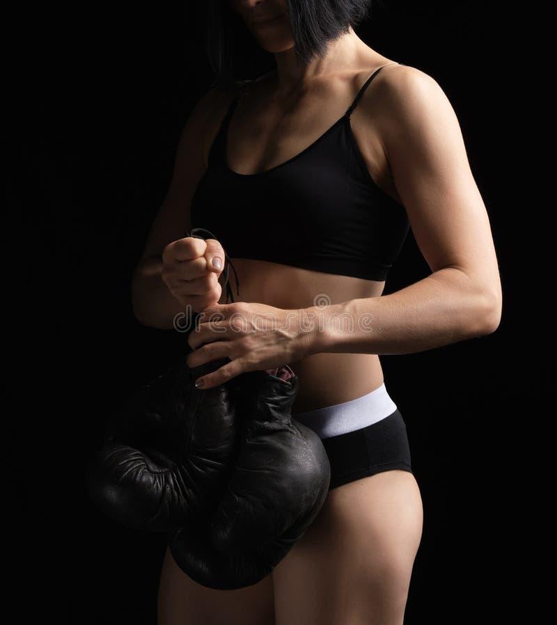 Jong meisje met zwarte haren en een musculair lichaam heeft een paar oude zwarte bokshandschoenen royalty-vrije stock afbeelding