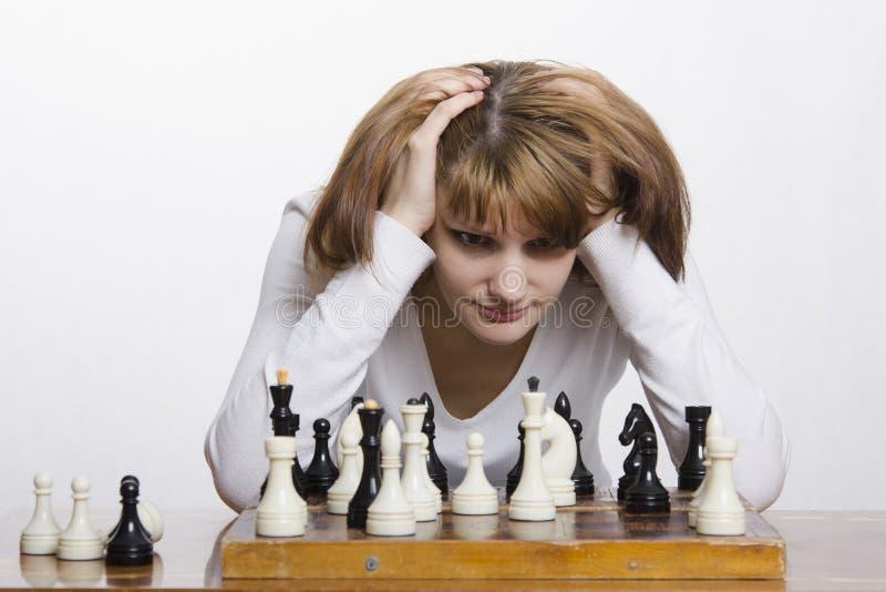 Jong meisje om een beweging tijdens het spel van schaak te overwegen stock afbeelding