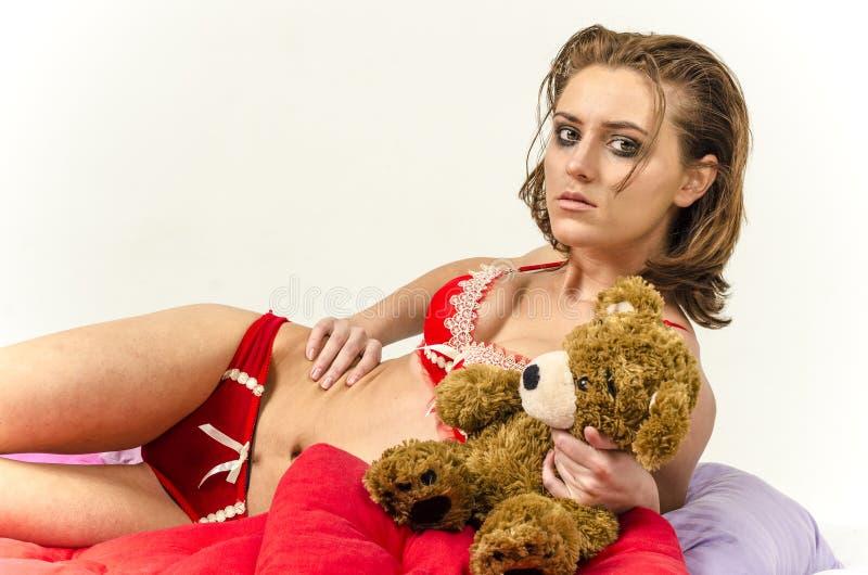 Jong meisje in ondergoed in bed schreeuwen en afvegende scheuren die haar handen smeren royalty-vrije stock fotografie