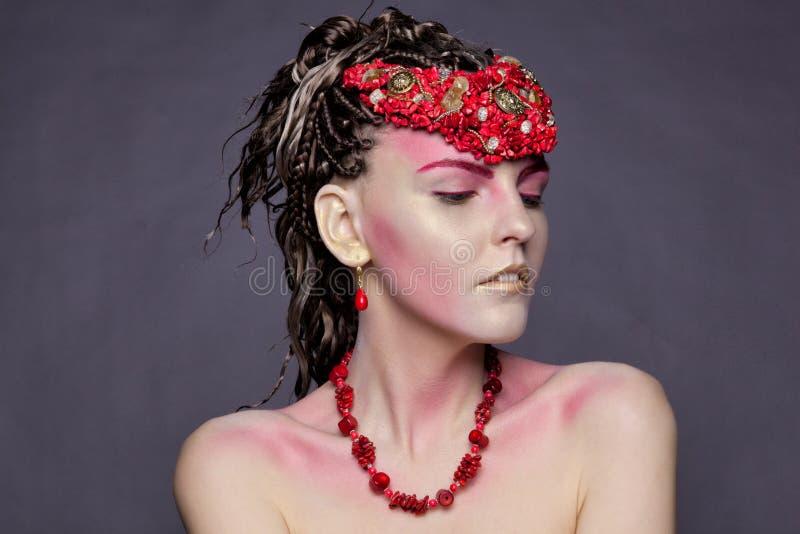 Jong meisje in oorringen en halsbanden van rood koraal stock afbeelding