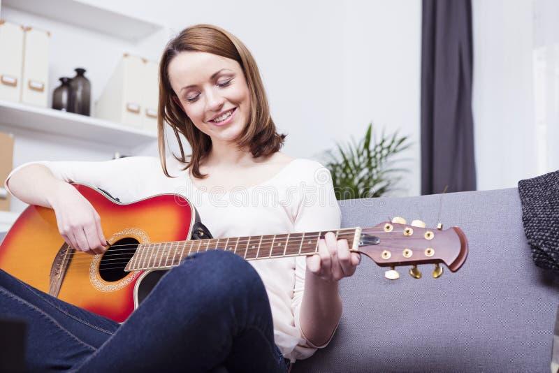 Jong meisje op bank het spelen gitaar royalty-vrije stock fotografie